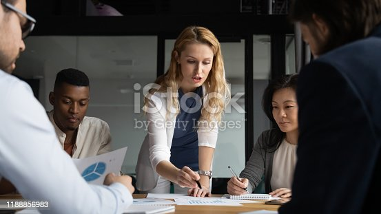 Concentrated young businesswoman explaining market research results in graphs to mixed race colleagues. Focused group of diverse employees holding brainstorming meeting, discussing project ideas.