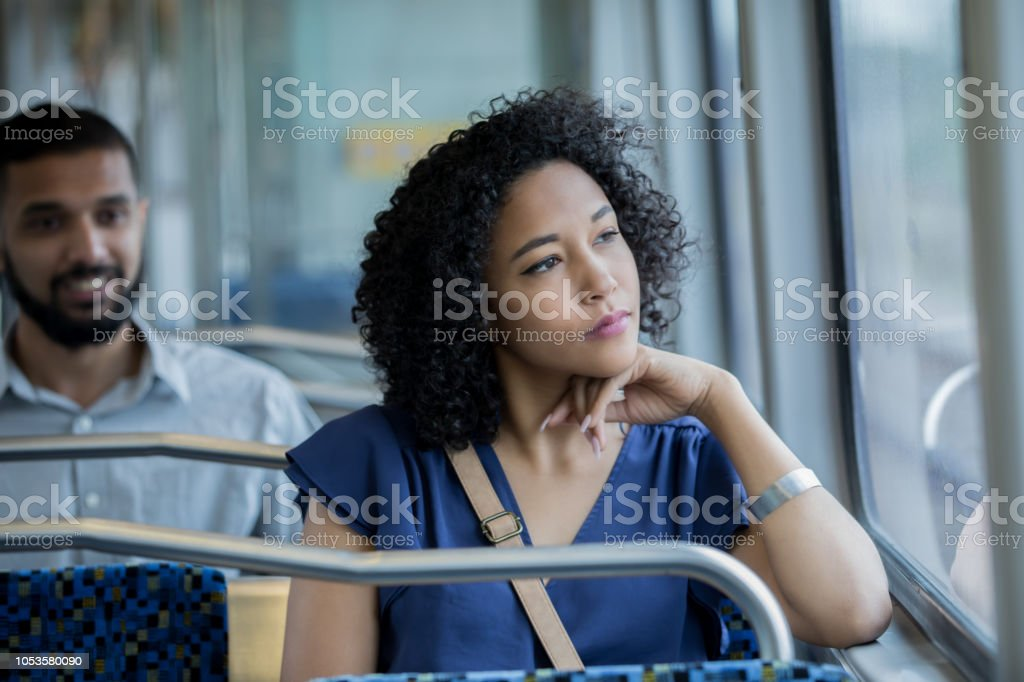 Young businesswoman gazing out window while riding public transportation commuter train stock photo