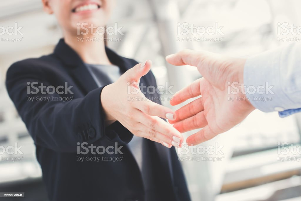 Young businesswoman going to make handshake with a businessman stock photo