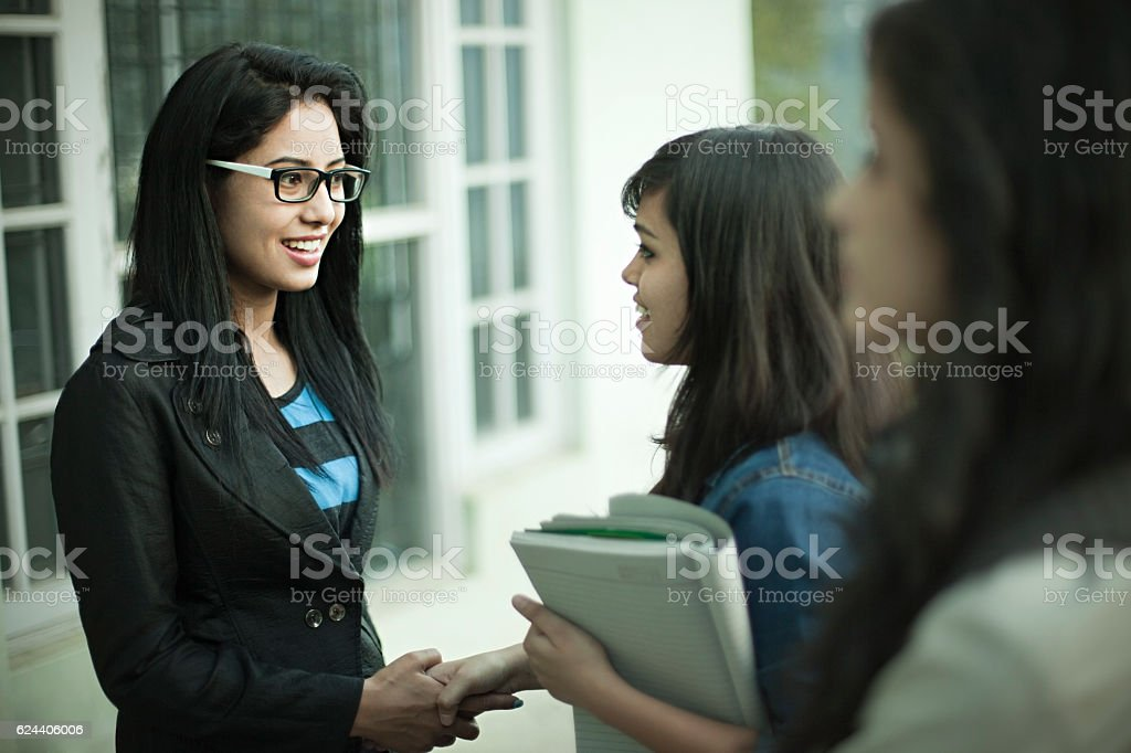 Young businesswoman greeting girls with handshake at office. stock photo