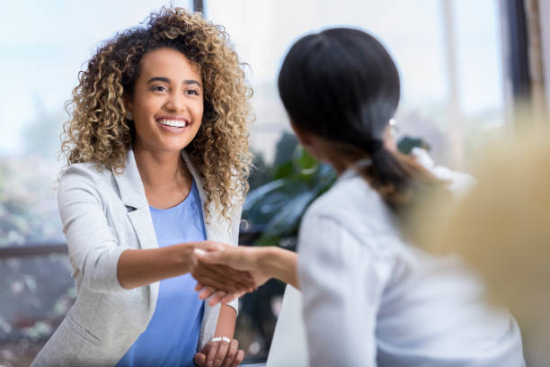 young businesswoman greets colleague - greeting stock pictures, royalty-free photos & images