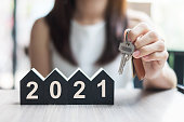 istock Young Businesswoman hands holding key and 2021 Happy New Year with house model on table office. New House, Financial, Property insurance, real estate, savings and New Year Resolution concepts 1227353691