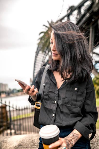 junge geschäftsfrau haben eine pause und schreiben etwas auf smartphone neben sydney harbour bridge - kaffeetasse tattoo stock-fotos und bilder