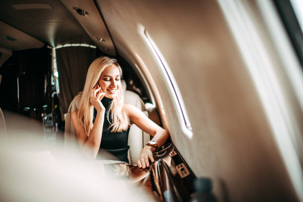 Young businesswoman having a conversation on a smart phone while traveling in a private jet stock photo