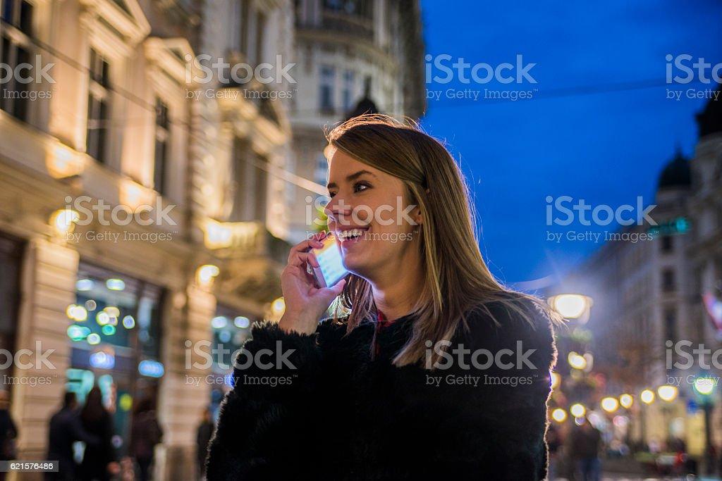 Young businesswoman having a conversation using a smartphone, night lights photo libre de droits