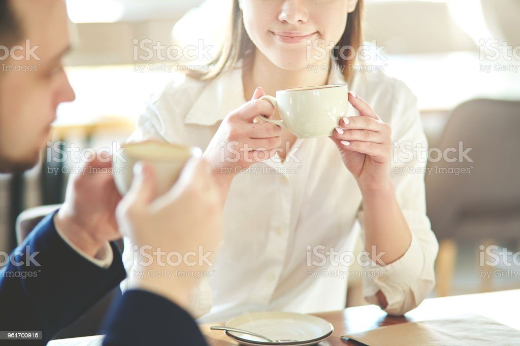 Young businesswoman having networking coffee meeting with male colleague. Two business people sitting at table in cafe with cups in their hands royalty-free stock photo