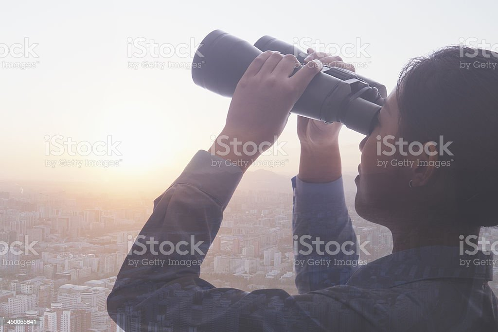 Young businesswoman holding binoculars over cityscape of Beijing stock photo