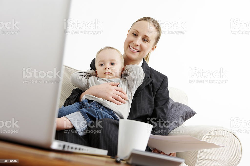 Young businesswoman holding her baby while working royalty-free stock photo