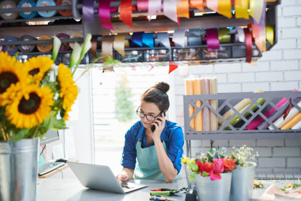 young businesswoman in flower shop - owner laptop smartphone foto e immagini stock