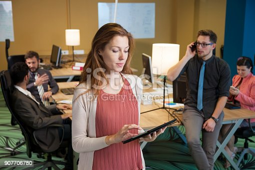 624700110istockphoto Young businesswoman in office with colleagues in background 907706780
