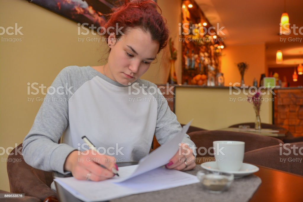A young businesswoman in the bar examines the documents while drinking coffee stock photo