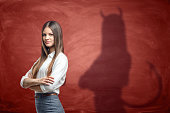 Young businesswoman is casting shadow of devil on rusty orange