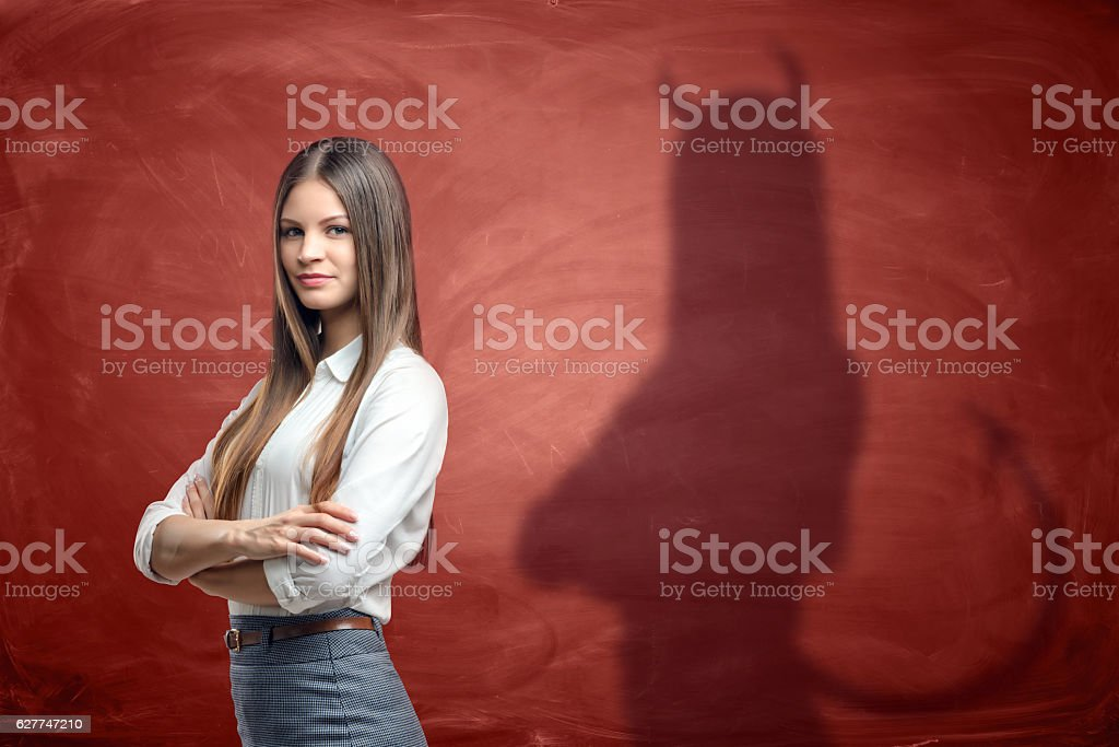 Young businesswoman is casting shadow of devil on rusty orange stock photo