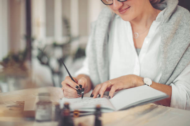 Young businesswoman is writing in a personal organizer - foto stock