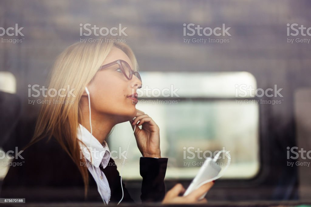 Young businesswoman listening music. Photo from outside. stock photo