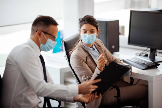 Young businesswoman listening to her male coworkers explanation stock photo stock photo