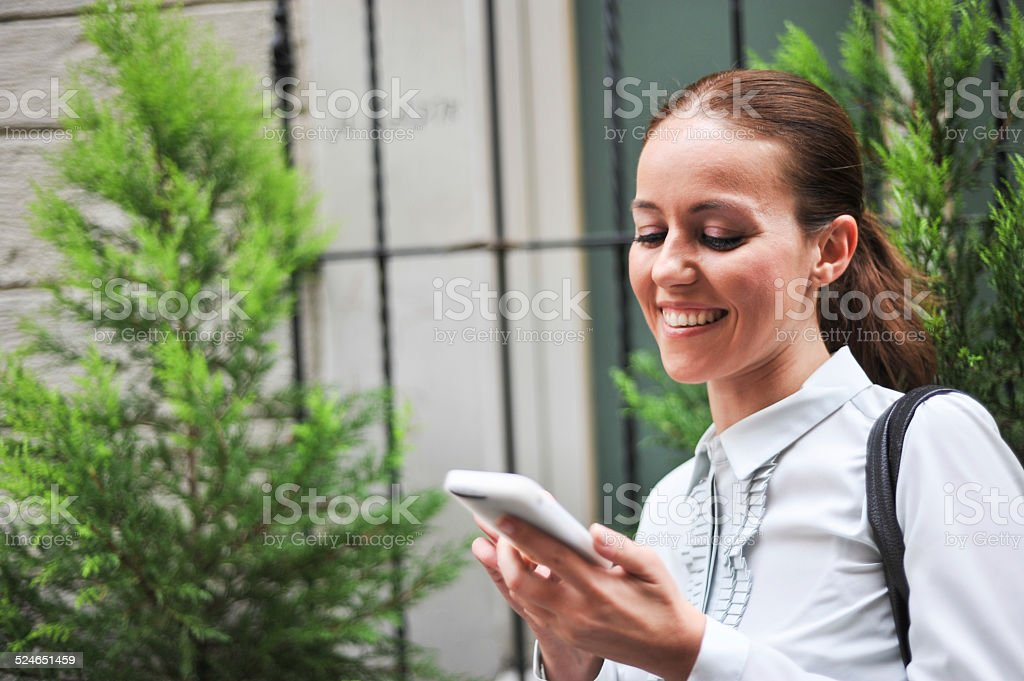 Young businesswoman looking at her mobile phone royalty-free stock photo