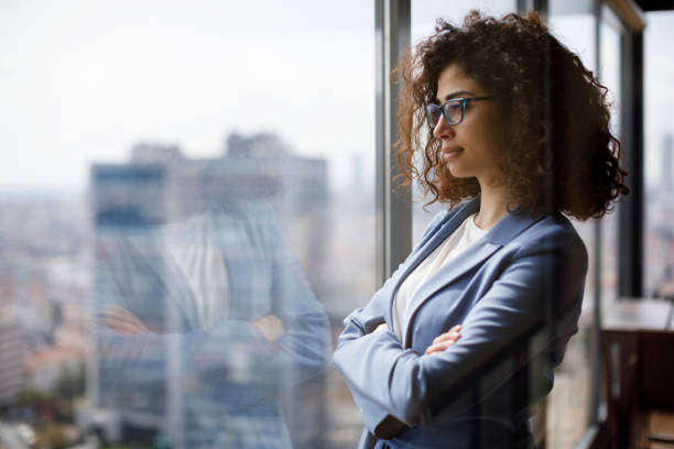 Young businesswoman looking through window Young businesswoman looking through window the way forward stock pictures, royalty-free photos & images