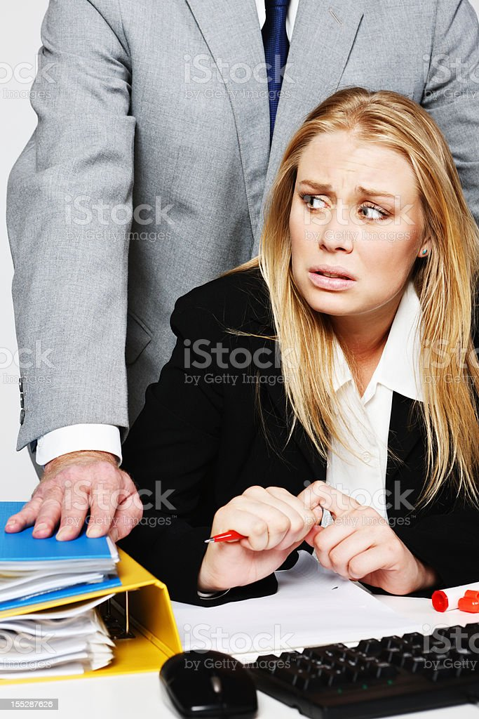 Young businesswoman looks round nervously at harassing man behind her stock photo