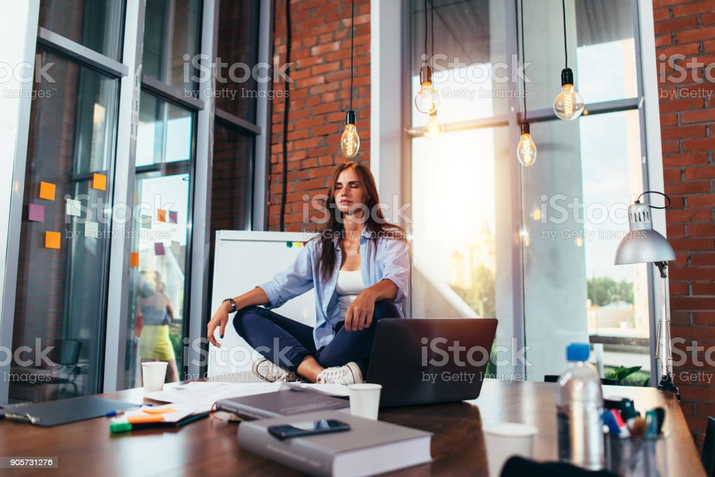 Young businesswoman meditating sitting on working table in lotus pose in her office stock photo