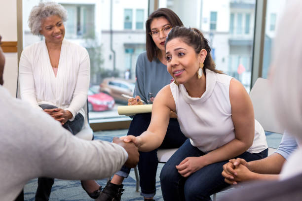 Young businesswoman meets new client A serious young businesswoman sits with colleagues and reaches forward to shake hands with an unseen new client. encouragement stock pictures, royalty-free photos & images