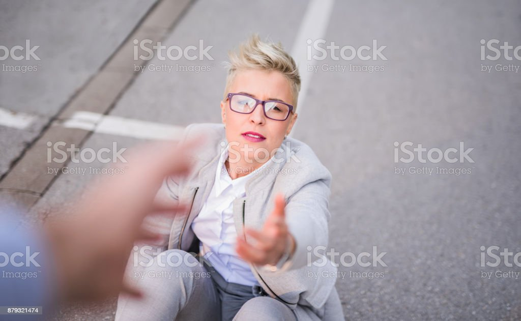 Young businesswoman needs help to get back on her feet. stock photo