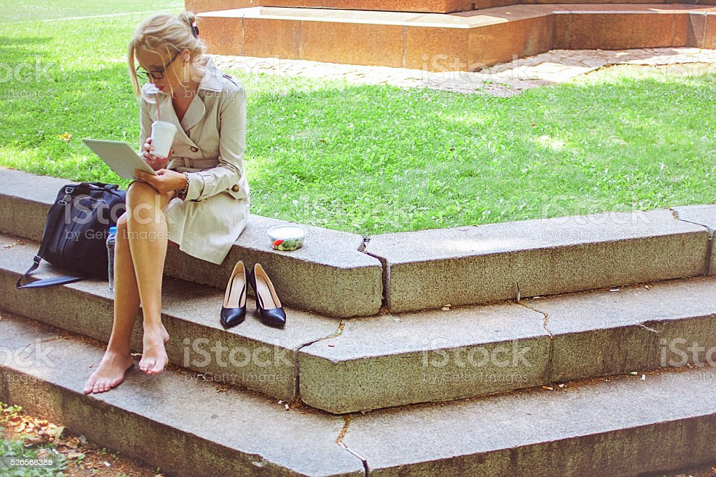Young businesswoman on a lunch break in park stock photo