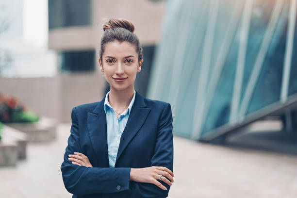 Young businesswoman Portrait of a smiling businesswoman standing with arms crossed lawyer stock pictures, royalty-free photos & images