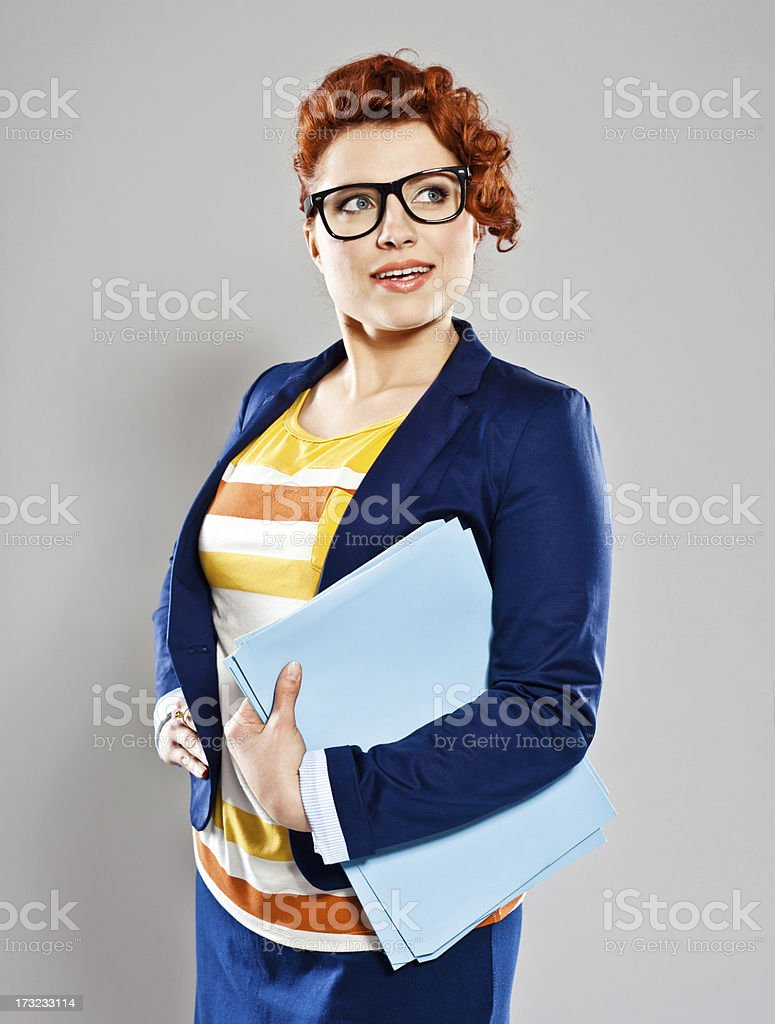 Young businesswoman Portrait of confident businesswoman, looking away and smiling. Studio shot, grey background. 25-29 Years Stock Photo