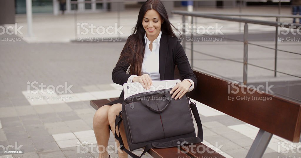 Young businesswoman placing her laptop in a bag stock photo
