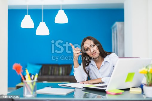 istock Young businesswoman pointing with her finger 816423840