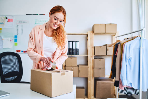Young businesswoman  preparing deliveries in small office stock photo
