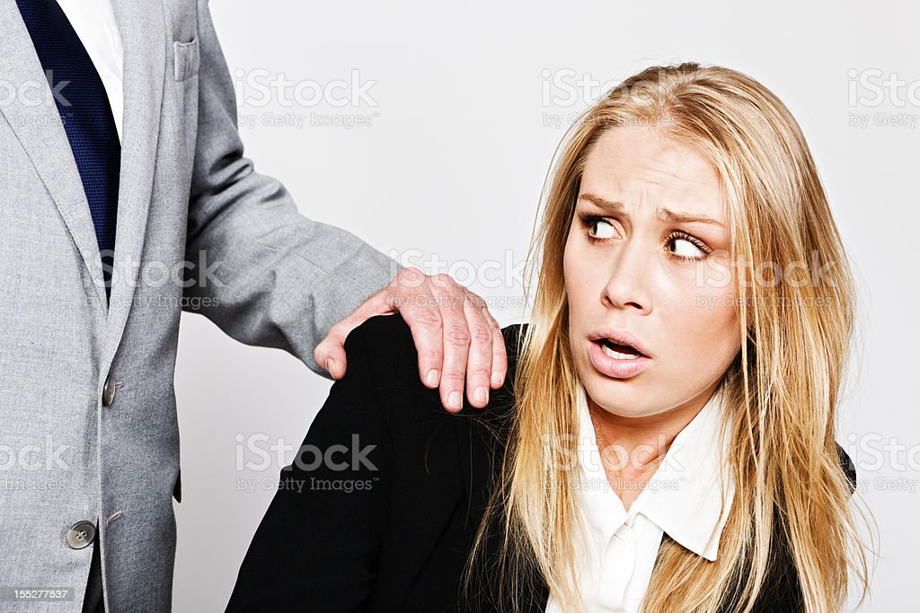 Young businesswoman pulls away from unwelcome touch by mature businessman stock photo