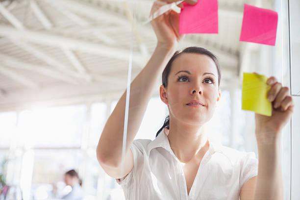 Junge Geschäftsfrau putting-Klebstoff Notizen auf Glaswand im Büro – Foto