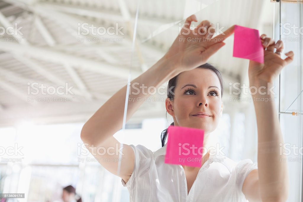 Young businesswoman putting sticky notes on glass wall in office stock photo