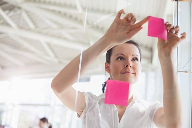 Junge Geschäftsfrau setzen Klebezettel auf Glaswand im Büro – Foto