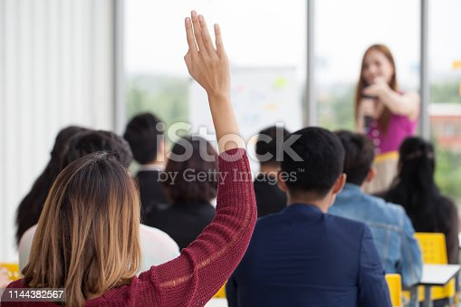 istock young businesswoman raising hand  to question from Speaker in Seminar. Group Meeting . Conference  Concept . Rear back view 1144382567