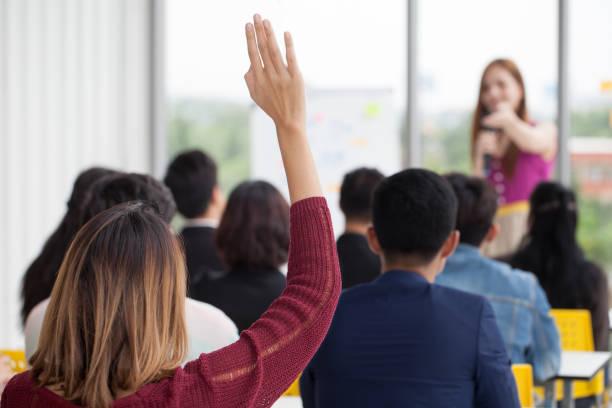 young businesswoman raising hand  to question from speaker in seminar. group meeting . conference  concept . rear back view - formazione degli adulti foto e immagini stock