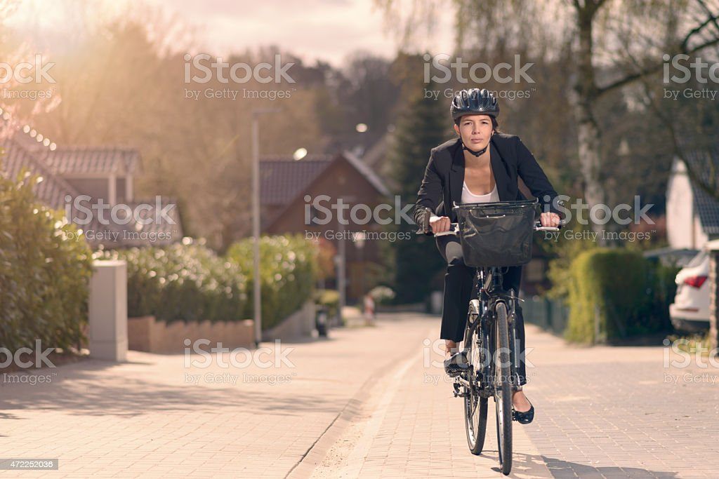 Young businesswoman riding to work on a bicycle stock photo