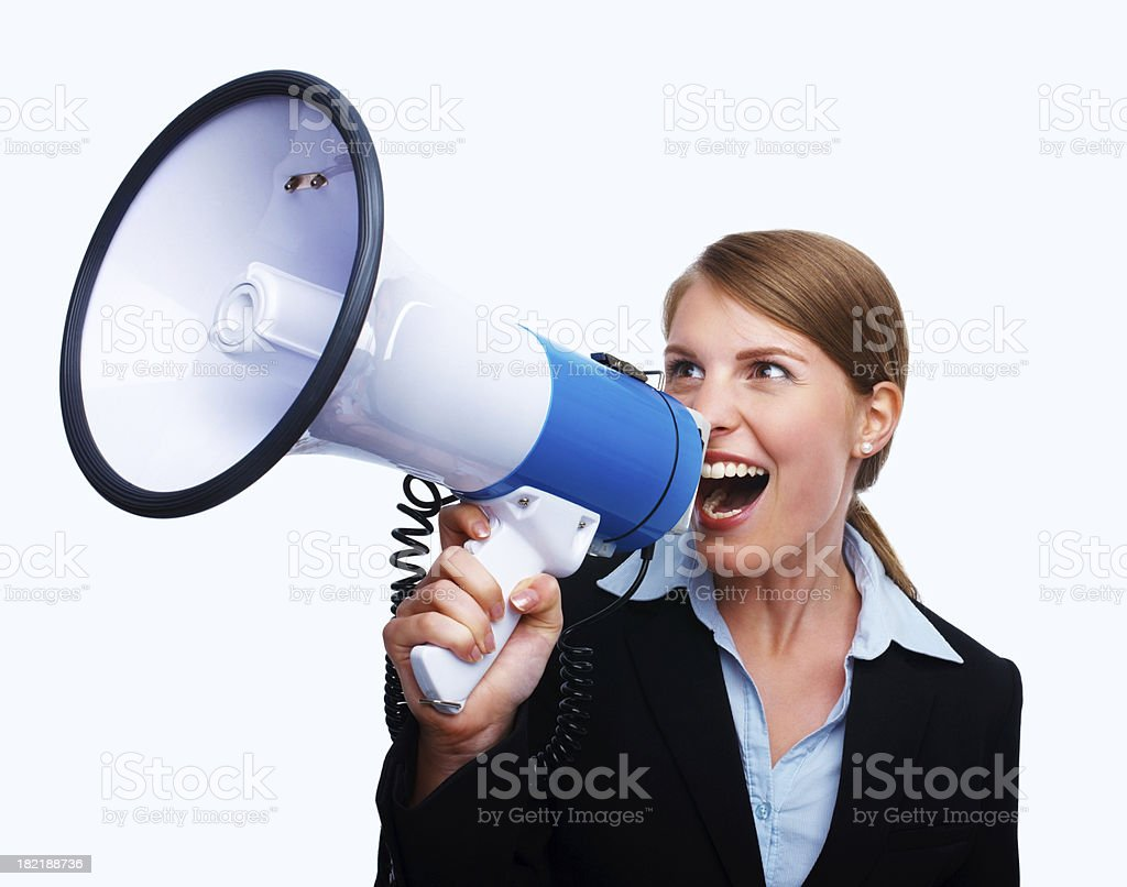 Young businesswoman shouting into a megaphone royalty-free stock photo