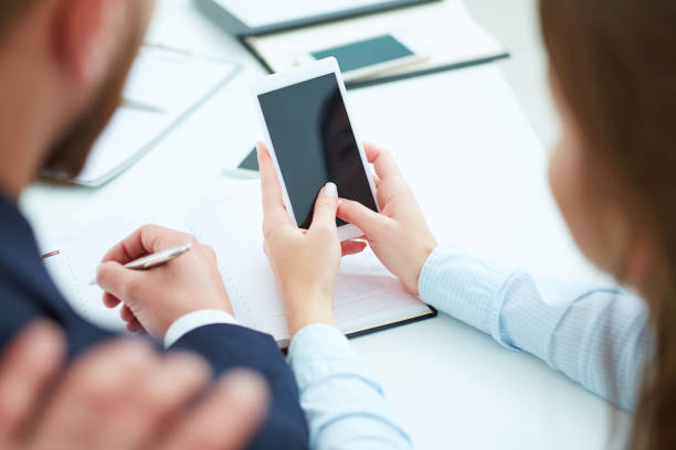 Young businesswoman showin phone screen to colleagues in office. stock photo