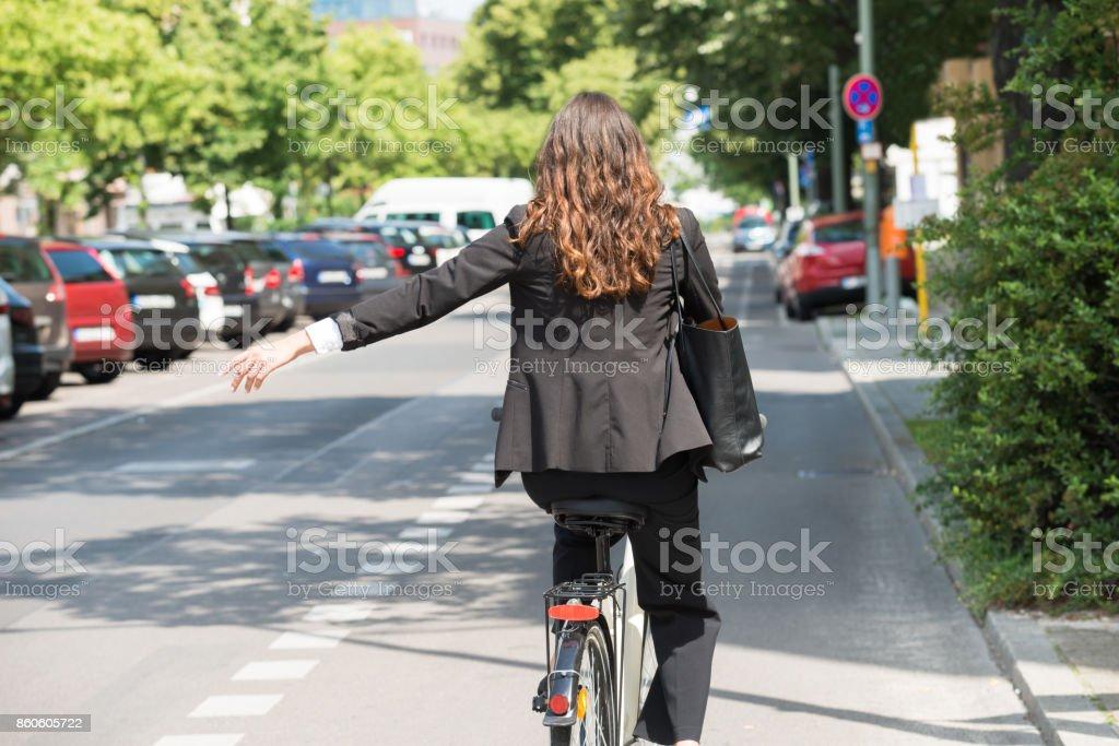 Joven empresaria mostrando a su vez en bicicleta - Foto de stock de Adulto libre de derechos