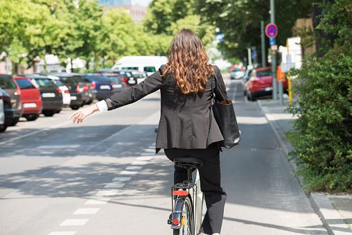Joven Empresaria Mostrando A Su Vez En Bicicleta Foto de stock y más banco de imágenes de Adulto