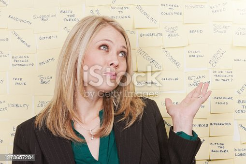 Woman looks confused by all the business jargon behind her.