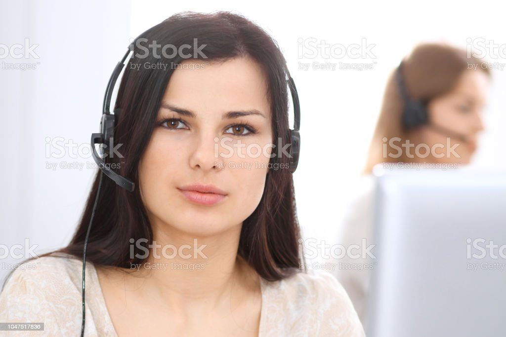 Young businesswoman sitting at desk and while consulting clients....