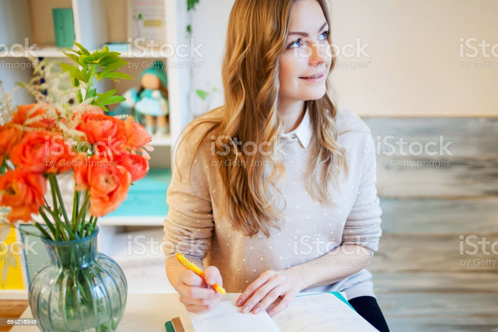 Young businesswoman sitting at desk and working. Beautiful woman fills planner royalty-free stock photo