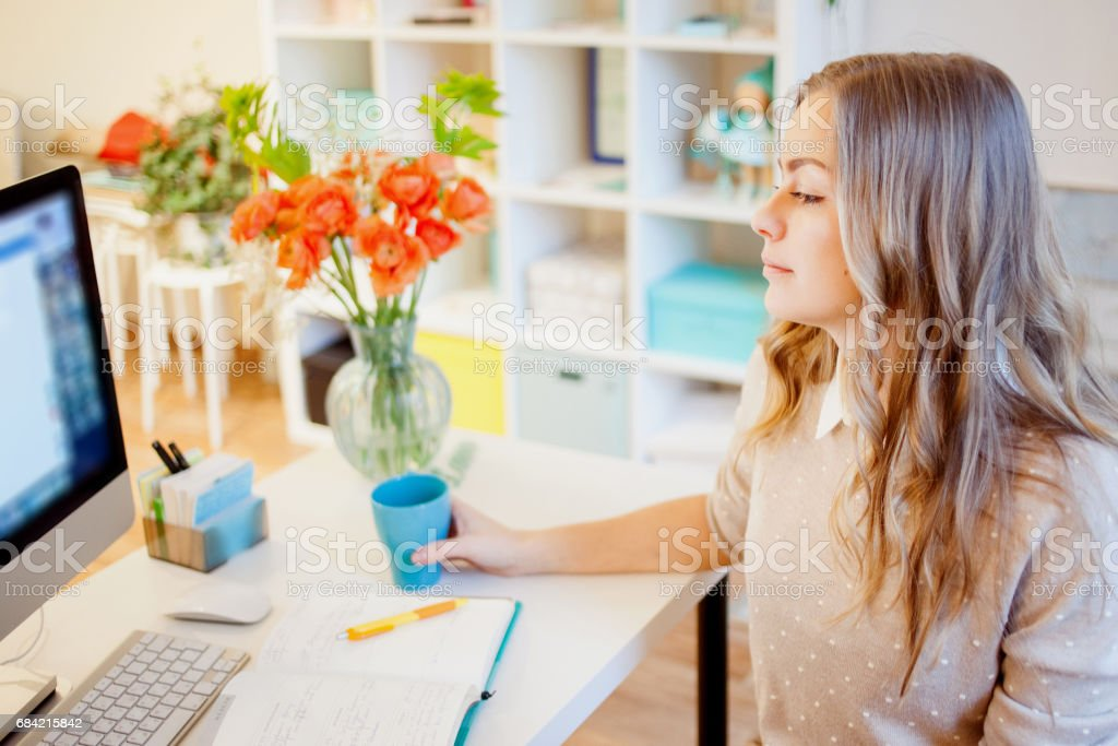 Young businesswoman sitting at desk and working. Beautiful woman drinking coffee. Start the day royalty-free stock photo