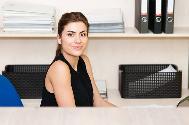 молодая деловая женщина, сидящая на стол и работы. - vlad models стоковые фото и изображения