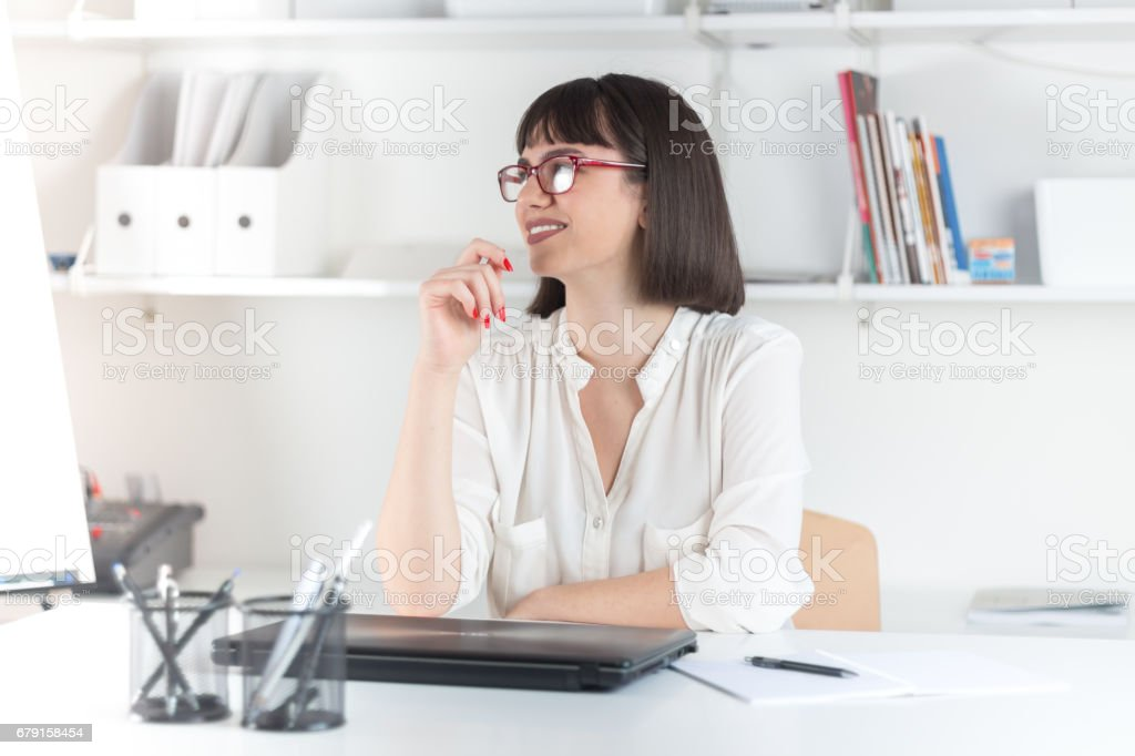 Young businesswoman sitting at desk and working photo libre de droits
