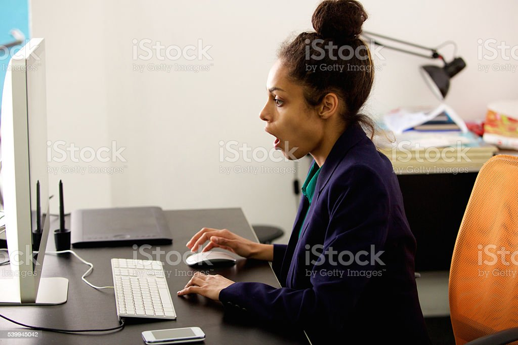 Young businesswoman sitting at her desk looking surprised stock photo